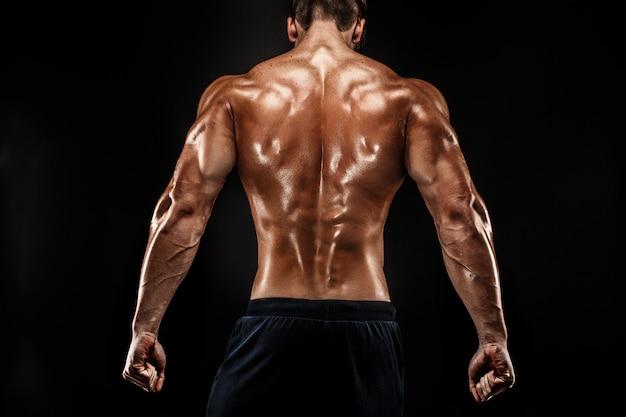 Vista posterior del hombre irreconocible, músculos fuertes posando con los brazos hacia abajo