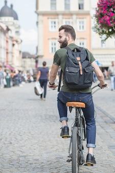 Vista posterior de un hombre joven que monta la bicicleta en la ciudad