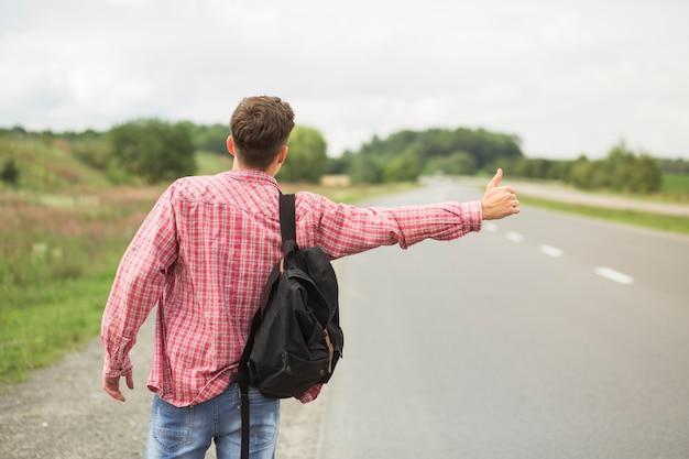 Vista posterior del hombre joven con su mochila haciendo autostop en el camino recto