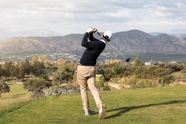 Vista posterior del hombre jugando al golf en el campo