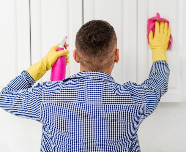 Vista posterior del hombre limpiando gabinetes de cocina