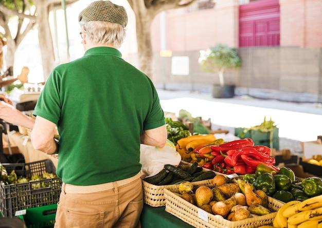 Vista posterior del hombre mayor de pie en el puesto de verduras y frutas