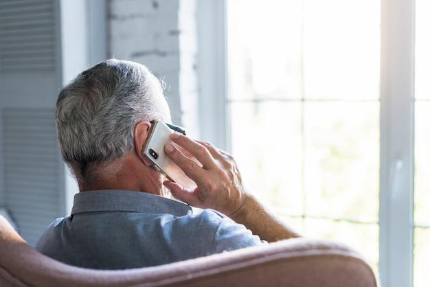 Vista posterior del hombre mayor que habla en el teléfono móvil