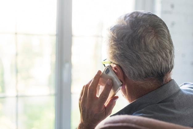 Vista posterior del hombre mayor que usa el teléfono móvil