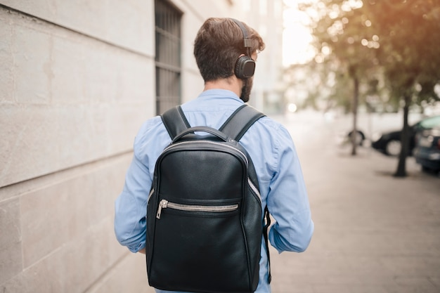 Vista posterior de un hombre con mochila caminando sobre el pavimento