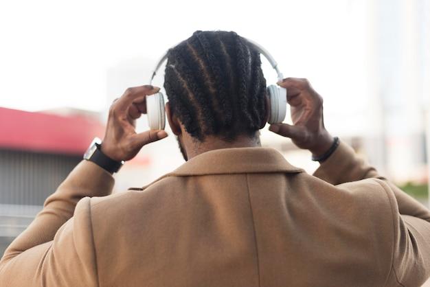 Vista posterior del hombre moderno escuchando música a través de auriculares