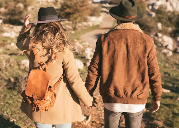 Vista posterior hombre y mujer tomados de la mano afuera
