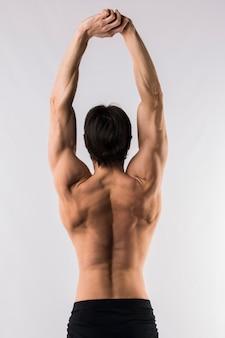 Vista posterior del hombre musculoso sin camisa con los brazos arriba