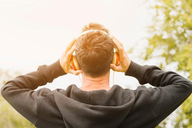 Vista posterior de un hombre en la música que escucha sudadera con capucha negra en los auriculares en el parque
