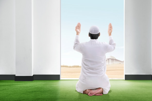 Vista posterior del hombre musulmán asiático sentado en posición de oración en la alfombra, levanta la mano y mira el cielo desde el interior de la habitación