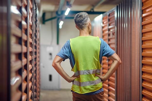 Vista posterior del hombre de pie en el almacén