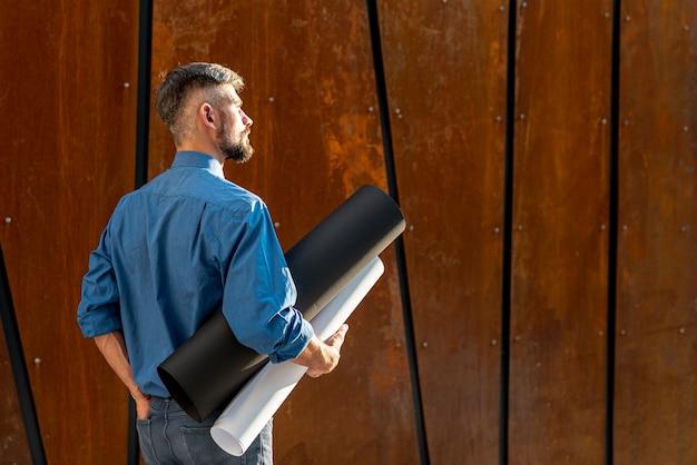 Vista posterior del hombre con plan de construcción
