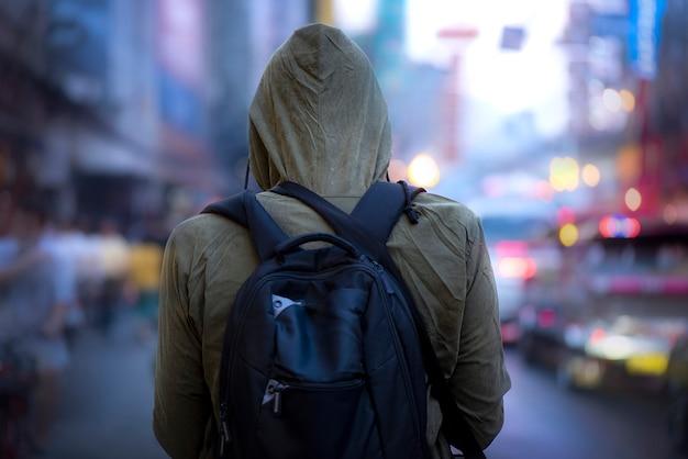 Vista posterior del hombre posando con capucha de invierno en carretera
