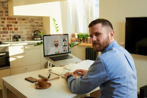 Vista posterior de un hombre que se distrajo durante una conversación con colegas por una videollamada.