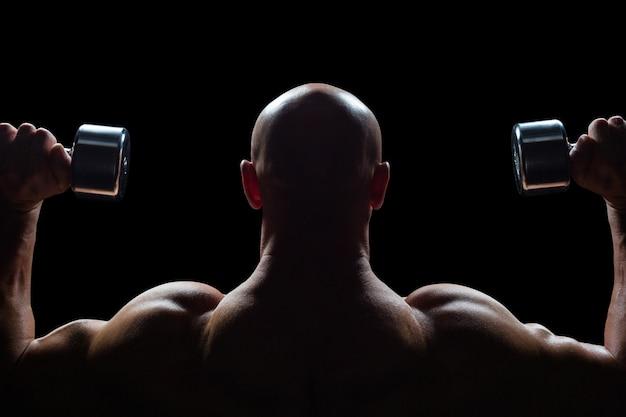 Vista posterior del hombre que ejercita con pesas de gimnasia