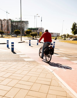 Vista posterior de un hombre que monta la bicicleta en la calle en la ciudad