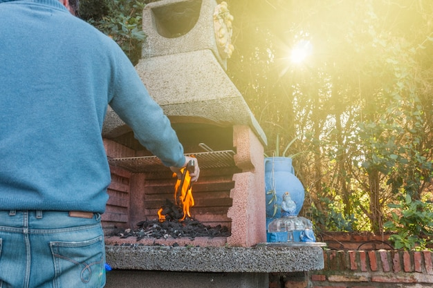 Vista posterior de un hombre quemando carbón en la barbacoa
