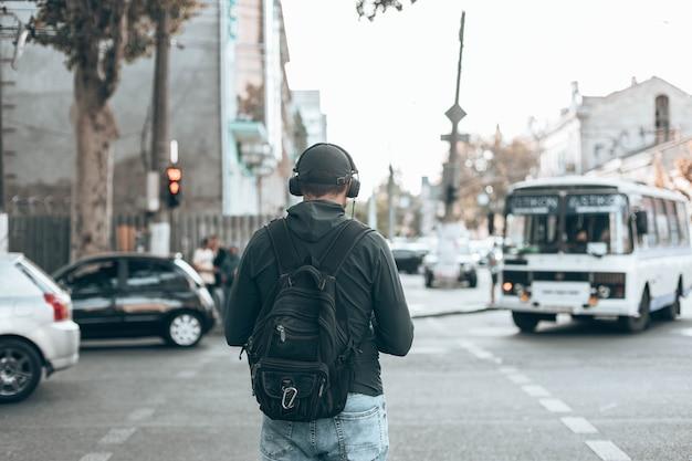 Vista posterior del hombre en ropa casual con una mochila escuchando música en auriculares en la calle al aire libre