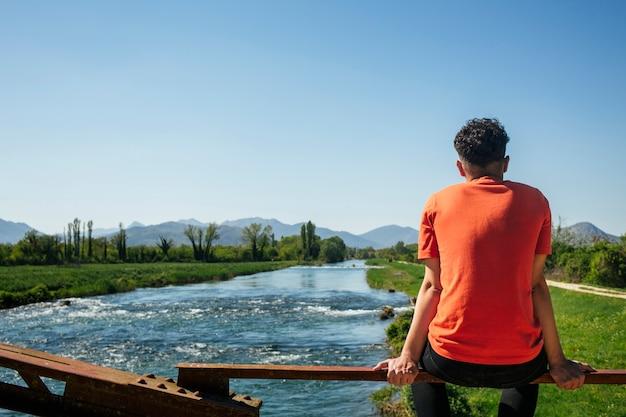 Vista posterior del hombre sentado en la barandilla cerca del río idílico
