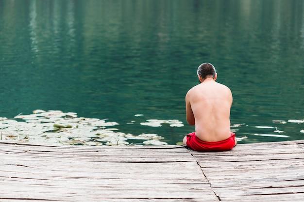 Vista posterior de un hombre sentado en el borde del muelle de madera cerca del lago