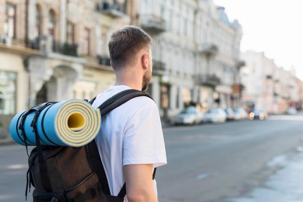Vista posterior del hombre turista con mochila