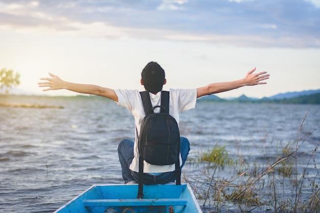 Vista posterior del hombre de viaje con mochila sentado en la cola del bote con vistas al lago y a la montaña, trave