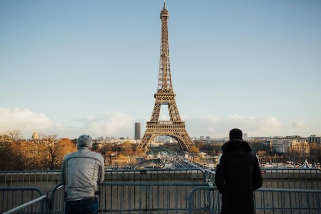 Vista posterior de los hombres jóvenes de viaje en la zona de trocadero con la torre eiffel