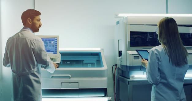 Vista posterior de los hombres y mujeres científicos médicos caucásicos que trabajan en el laboratorio en la computadora y la tableta. posterior.