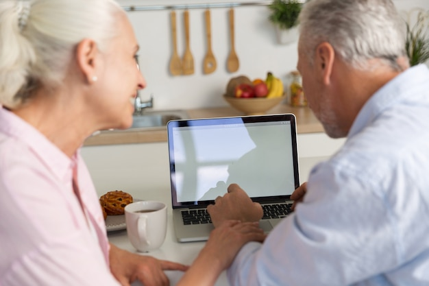 Vista posterior de la imagen de la pareja madura amorosa familia usando laptop
