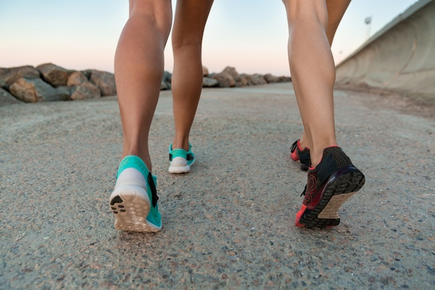 Vista posterior de la imagen recortada de dos mujeres jóvenes en zapatillas de deporte
