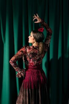 Vista posterior impresionante bailarina de flamenca levantando la mano