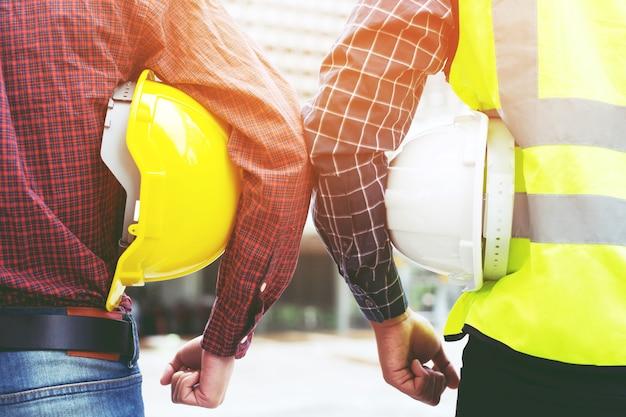 Vista posterior de la ingeniería masculina dos trabajador de la construcción sosteniendo un casco amarillo de seguridad y un casco blanco con ropa reflectante de cerca