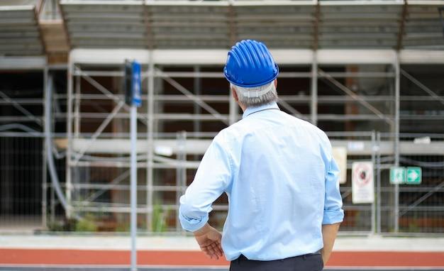 Vista posterior de un ingeniero mirando un edificio en construcción