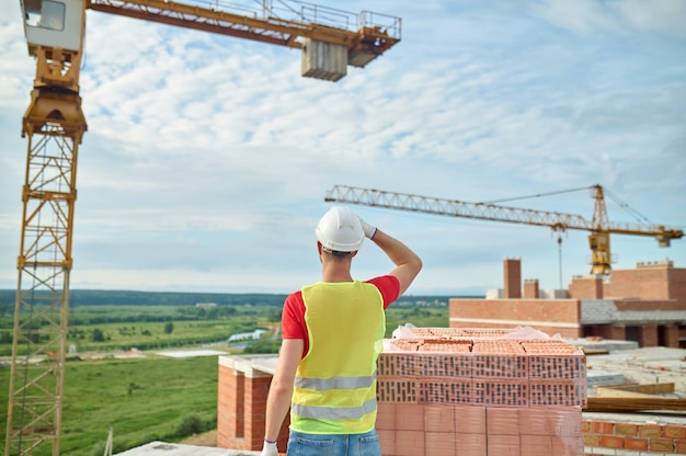 Vista posterior de un ingeniero profesional con un casco protector y un chaleco reflectante inspeccionando el sitio de construcción