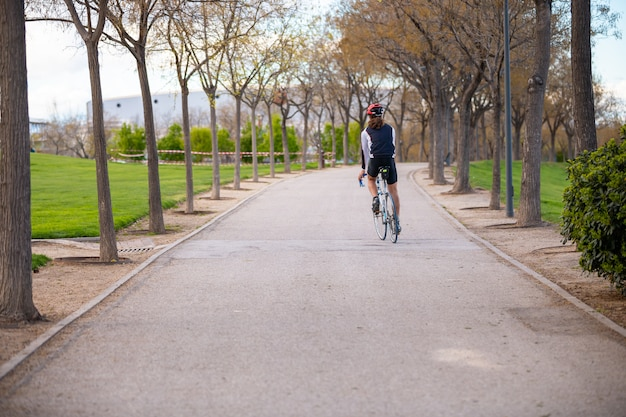 Vista posterior del joven ciclista masculino en ropa deportiva y casco protector bicicleta ciclismo en carretera en el parque