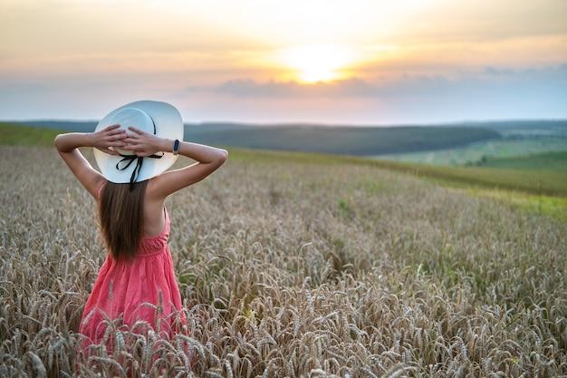 Vista posterior de la joven feliz en vestido rojo de verano y sombrero de paja de pie en la pradera de la granja amarilla con trigo dorado maduro levantando sus manos disfrutando de la cálida noche.