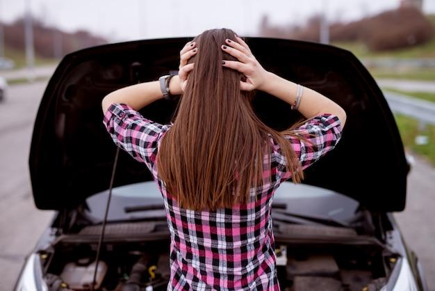 La vista posterior de una joven hermosa estresada está mirando debajo del capó de su automóvil y sosteniendo su cabeza con desesperación.