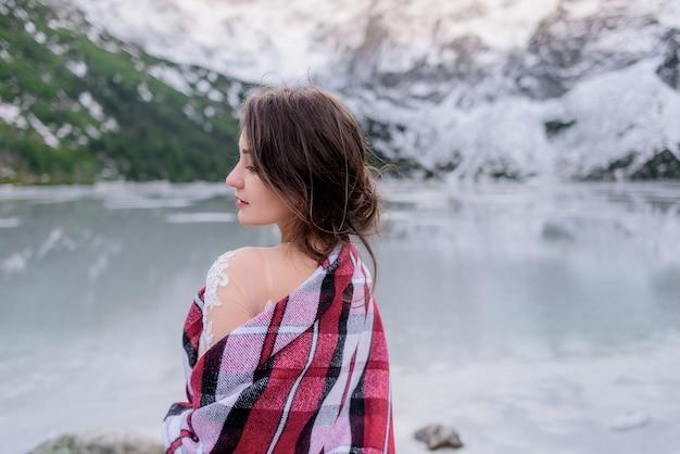 Vista posterior de la joven morena en las montañas de invierno cerca del lago congelado