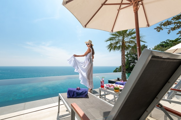 Vista posterior: joven morena rizada con una capa blanca y traje de baño posando cerca de la piscina, tumbonas y una sombrilla de playa