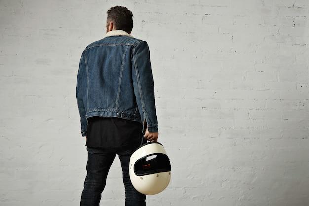 Vista posterior del joven motorista viste una chaqueta de mezclilla de piel de oveja y una camiseta henley negra en blanco, caminando y sostiene un casco de motocicleta beige vintage, aislado en el centro de la pared de ladrillo blanco