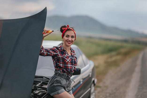 La vista posterior de la joven en pantalones cortos de mezclilla cortos grises está reparando el coche.