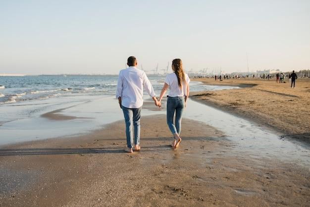 Vista posterior de una joven pareja caminando cerca de la costa en la playa