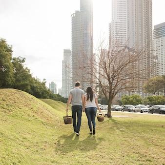 Vista posterior de la joven pareja caminando cerca del parque de la ciudad