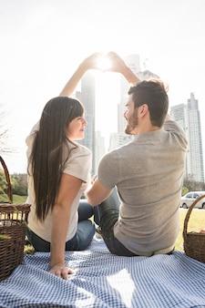 Vista posterior de la joven pareja haciendo forma de corazón con la mano en la luz del sol en picnic