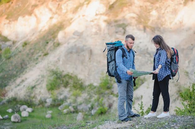 Vista posterior de la joven pareja de mochileros con grandes mochilas cogidos de la mano