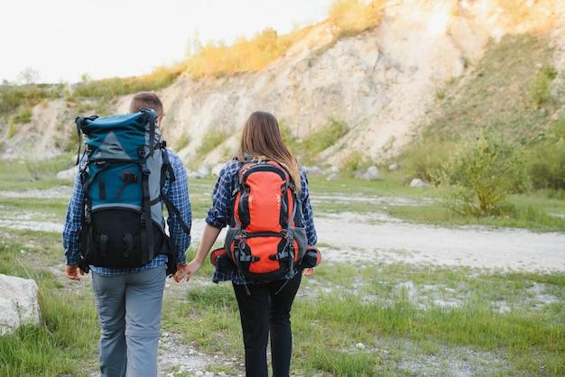 Vista posterior de la joven pareja de mochileros con grandes mochilas tomados de la mano y caminando por una carretera con una hermosa montaña