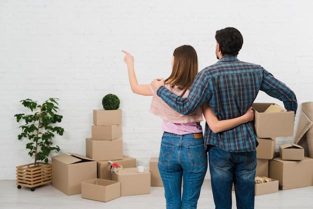 Vista posterior de la joven pareja de pie frente a cajas de cartón mirando una pared blanca pintada
