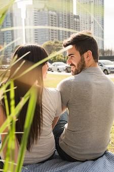 Vista posterior de la joven pareja sentada en el parque