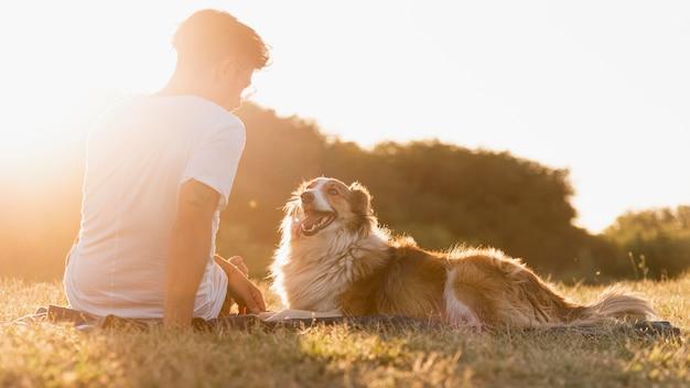 Vista posterior joven con perro en la playa