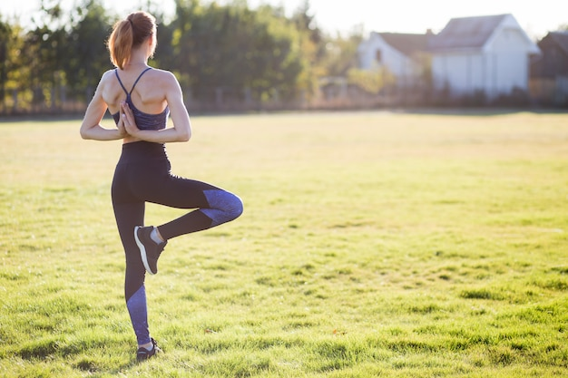 Vista posterior de la joven en posición de yoga medita en el campo al amanecer